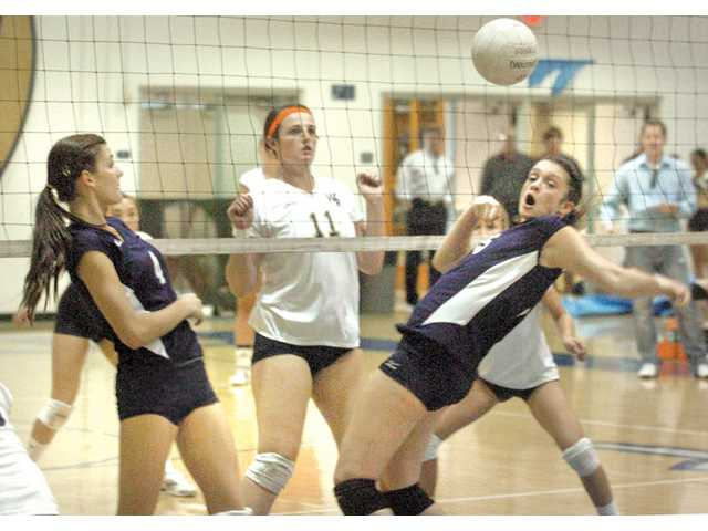Saugus middle blocker Ashley Pagan, right, goes for the ball as teammate Kristen McCord, left, and West Ranch middle blocker Bree Braucher (11) look on at Saugus High School on Thursday. The Centurions won the match 3-0.