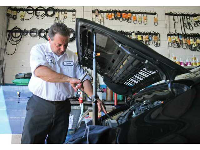 Frank Cervetto works on a 1997 Porsche 911 Carrera 2 at his Continental Motorcars shop Thursday afternoon.