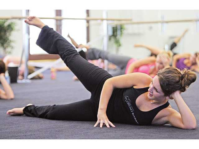 Leah Powers, 20, does a leg exercise during a Monday-morning class at Cardio Barre in Newhall.