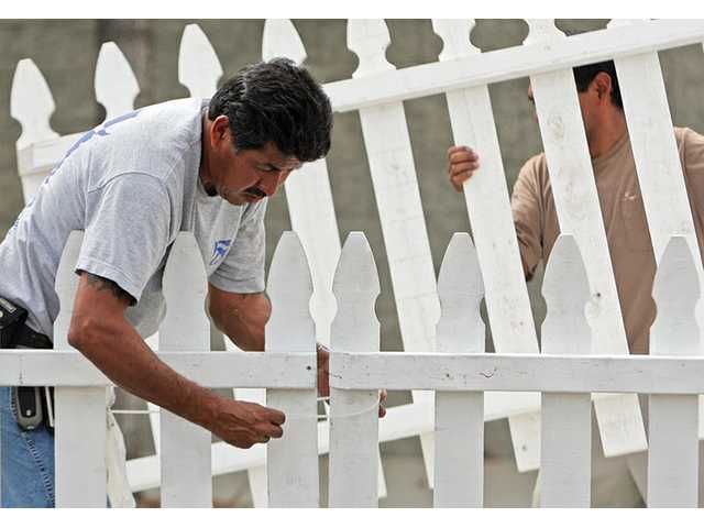 Alfredo Gonzalez, front, and Luis Mojica, employees of Avalon Tent & Party help set up fencing Friday for this weekend's Festival of the Arts, hosted by the city of Santa Clarita.