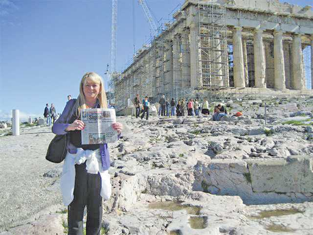 Sally Bond-Wolf of Realty Executives holds up a copy of The Signal at the Acropolis in Athens, Greece, during a recent trip.