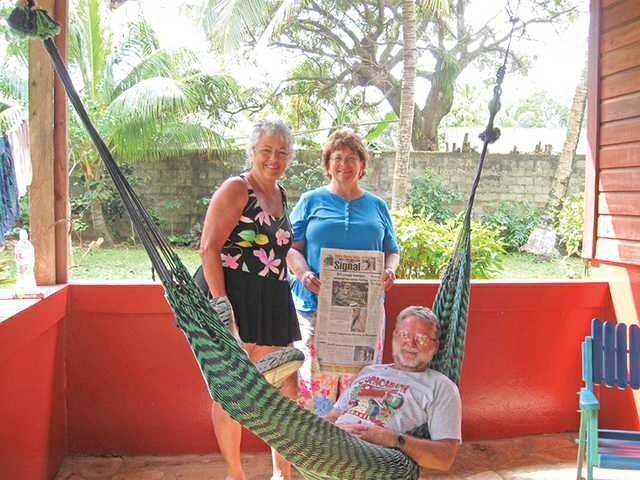 "Pat Willett, Sharon Dawson and Chuck Willlett relax on the patio of their chateau with a copy of the newspaper on Corn Island off the Carribean side of Nicaragua. The ""Three Mosquiteers"" joined a work party from Valencia United Methodist Church to help build homes for the people of Project Chacocente."