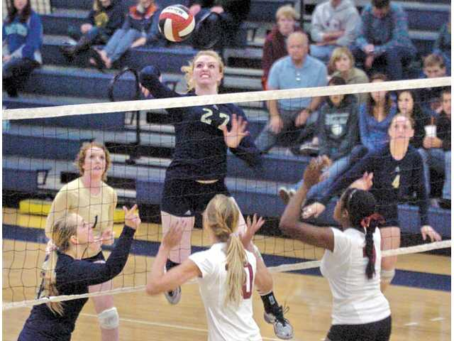 The Master's College middle blocker Victoria Callihan (27) spikes the ball over the net against the Westmont Lady Warriors at The Master's College on Tuesday. TMC won 3-2.