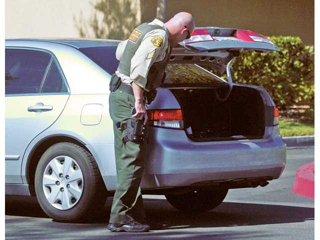 A deputy from the Santa Clarita Valley Sheriff's Station inspects a car trunk leaving Vons parking lot across from the Best Buy on the corner of Bouquet Canyon Road and Newhall Ranch Road in Santa Clarita on Thursday.