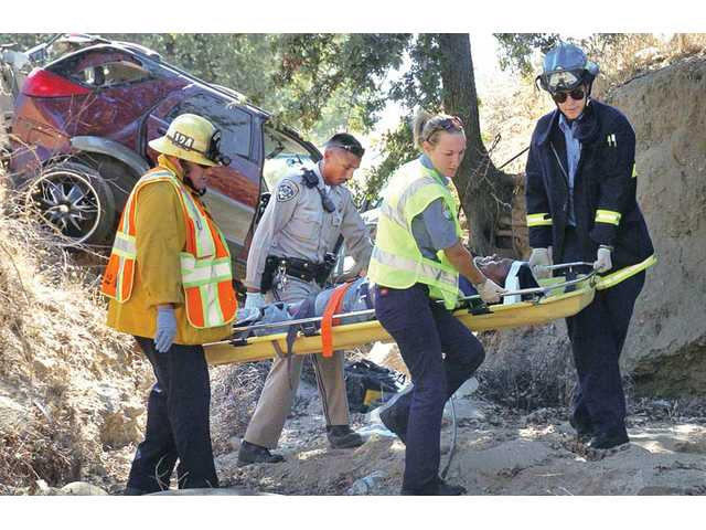 Emergency personnel carry a woman to an ambulance after her Buick Rendezvous careened into a ditch off the side of the northbound Interstate 5 Freeway near McBean Parkway just before noon on Saturday in Santa Clarita.
