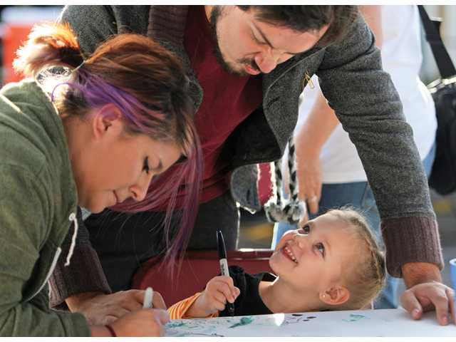 Brandi Cottengim, right, looks up and smiles at Anthony Hanlon and her nanny Sara Gonzalez-Foote as they doodle at The Big Draw booth on Thursday at the Art Walk.