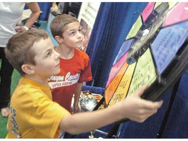 Taylor Torkelson, 8, left, and Mitch Gersh, 8, spin the wheel to win prizes at the booth of Back to Health Chiropractic Center at the expo. The expo began Friday and ran all weekend. It featured 107 exhibitor booths, food, entertainment, raffles and giveaways. L.A. Racing Experience provided a NASCAR vehicle and simulator.