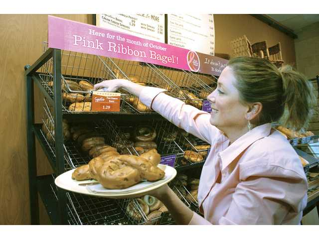 Local Panera Bread General Manager Katherine Stuart prepares a plate of pink-ribbon bagels, which are on sale for the month of October. A portion of proceeds go to the Susan G. Komen for the Cure organization.