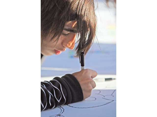 Newhall resident Cory Gomez, 17, a volunteer at the ARTree Community Arts Center, participates in The Big Draw, an international event that promotes drawing and art literacy for kids at the Art Walk event in the downtown Newhall on Oct. 7.