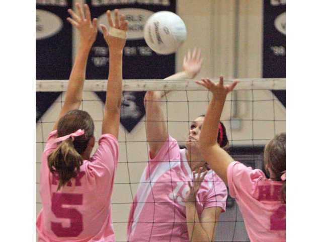 Saugus' Ashley Pagan, center, spikes the ball between Canyon's Morgan Fray, left, and Stevie Haubs on Thursday at Saugus.