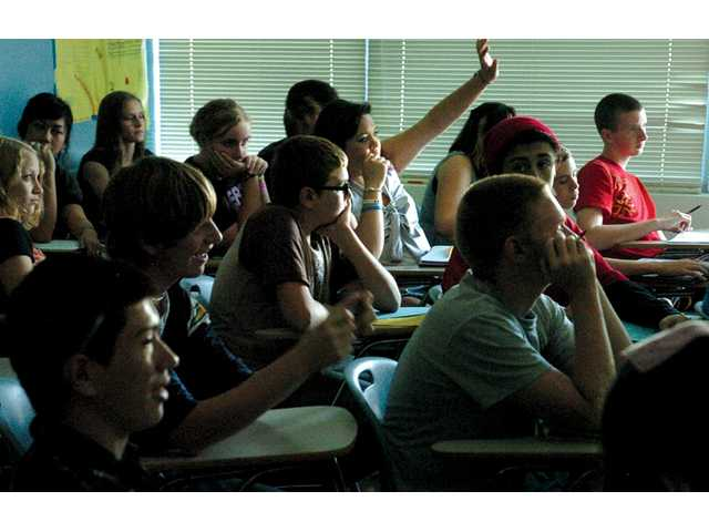 Tenth-grade students raise their hands during a recent chemistry lecture at Academy of the Canyons in Valencia.
