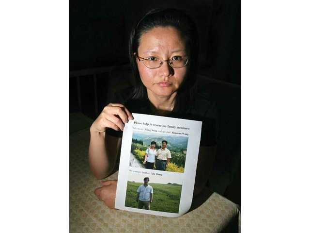 Canyon Country resident and Chinese immigrant Xiao Wang holds up pictures of her mother, Jiling Song; her father, Zhansuo Wang; and her brother Xia Wang. Wang's family members were held in a Chinese detention center for practicing Falun Gong, a series of meditative exercises. Wang's father is still imprisoned, and Wang is doing whatever she can to secure his release.