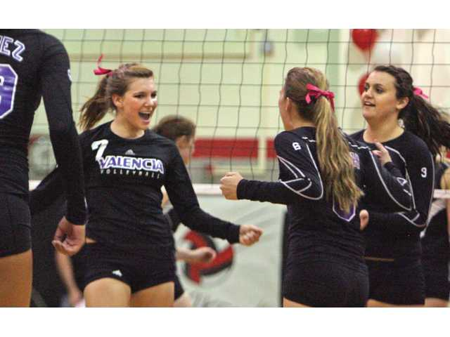 Valencia teammates Serena LeDuff (7), Jolie Stroh (6) and Alexa Schmidt, far right, celebrate a point during their match against Hart on Wednesday at Hart High School.