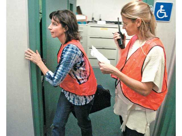 """Meadows Elementary teachers Michelle Vasquez, left, and Amy Sheen radio """"all clear"""" during Thursday's drill."""