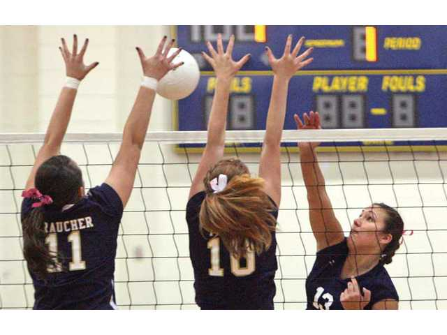 Saugus' Cory Nua, far right, spikes the ball over the net as West Ranch players Bree Braucher (11) and Julia Thomas (10) attempt a block on Thursday at West Ranch.