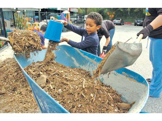 Jayden Medina, 3, dumps a load of mulch into a wheelbarrow as his parents and several other volunteers install a community garden at Santa Clarita Stepping Stones Children's Center in Newhall on Saturday.