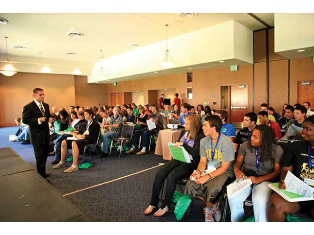 Brian Safdari speaks to students attending a youth leadership program at UCLA in August. Safdari's firm helps high school and college students learn how to successfully apply for financial aid and seek out colleges that endow students with greater financial assistance.