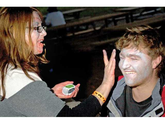 Hollie Rarick, of Santa Clarita, applies makeup to Michael Wiesen's face in preparation for the Zombie March.