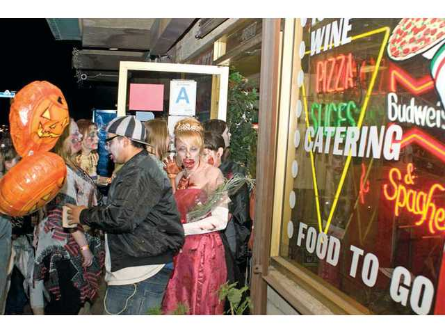 Zombies walk in and out of Maria's Deli in Newhall during the March.