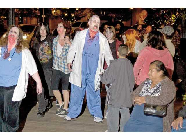 People dressed as zombies walk down Main Street in Newhall.
