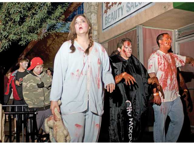 People portray zombies as they parade down Main Street in Newhall on Saturday. The second annual Main Street Zombie March was a fundraiser and canned food drive to benefit the Santa Clarita Valley Food Pantry.