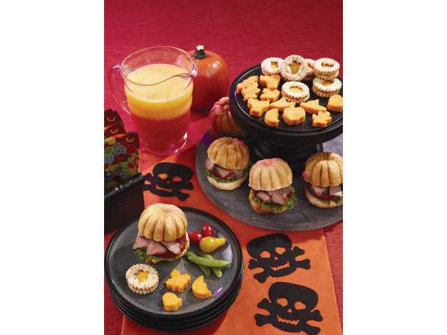Set a tempting, yet twisted table with sinister sunset cocktails, spooky crackers with savory cheese spread, magic polenta bites and flank steak on pumpkin-shaped rolls, which are surprisingly simple to make.