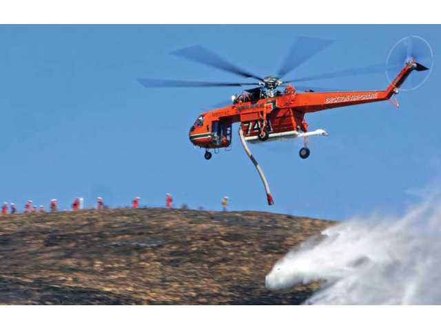 An Erickson Air-Crane makes a hillside water drop near an inmate crew on the side of Interstate 5 southbound lanes north of Lake Hughes Road in Castaic on Tuesday.  A 10-acre blaze, which erupted about 12:33 p.m., was contained by fire crews approximately one hour after it started, according to Los Angeles County Fire Department officials.