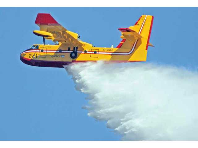 A CL-415 SuperScooper helps extinguish the wildfire Tuesday.