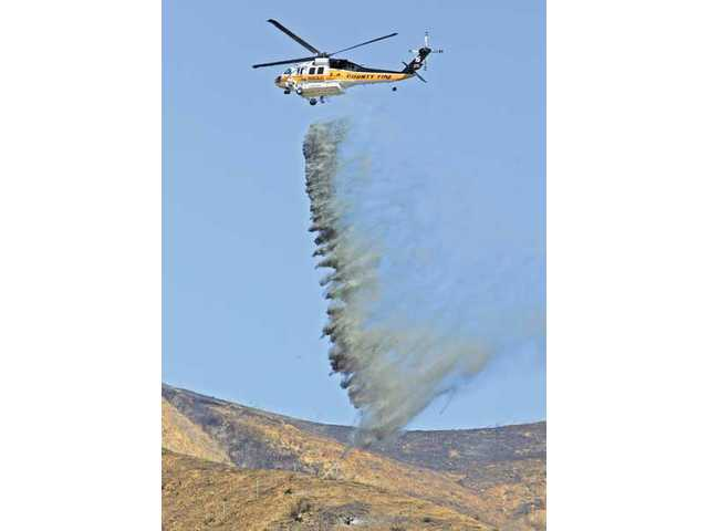 A Los Angeles County Fire Department helicopter drops water on a 10-acre brush fire in Castaic.