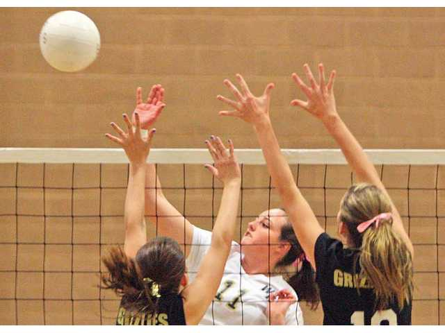West Ranch's Bree Braucher (11) hits the ball over the net as Golden Valley's Katie Nicholson, left, and Ashley Lorton defend on Thursday at Golden Valley High.