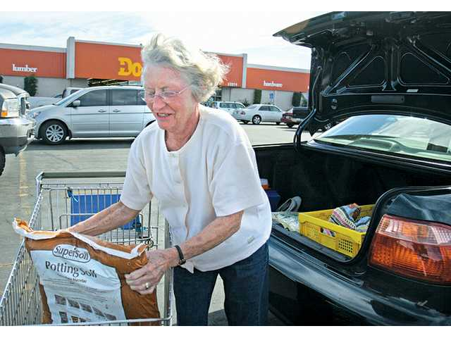 Inge York, of Valencia, loads her car with bags of potting soil that she purchased at the Do it Center on Thursday afternoon. The store, which is closing, has been in the SCV since the 1970s.