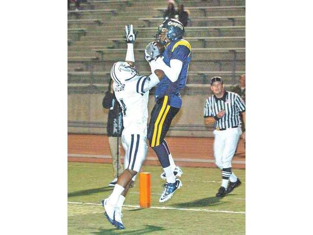 College of the Canyons receiver Rickeem Jackson, right, catches a touchdown pass against Cerritos College defensive back Ray Craig (4) on Saturday at Cougar Stadium.