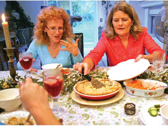 Friends Judy Albert, left, and Merry Graham enjoy a bounty of comfort foods at Graham's home in Newhall.