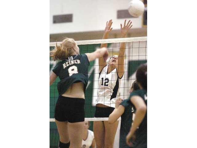 Saugus middle blocker Sarah Blomgren (12) deflects a shot by Canyon's Katelyn Reiner, left, on Tuesday at Canyon.