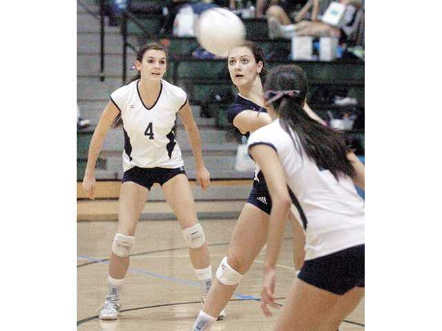 Saugus libero Maegan Wasserman, center, digs a ball as teammates Kristin McCord (4) and Jaclyn Clark look on at Canyon High School on Tuesday. The Centurions won 3-0.