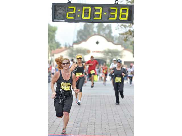 Michelle Unrot, 37, of Los Angeles, crosses the finish line of the half-marathon.