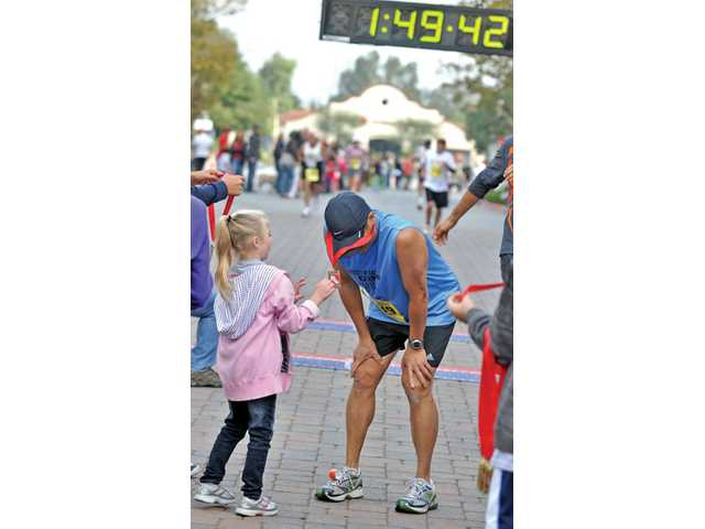 Kamrin Schultz, 6, puts a medal around 53-year-old Larry Wong's hat after he finishes the Santa Clarita half-marathon on Sunday at Westfield Valencia Town Center in Valencia.
