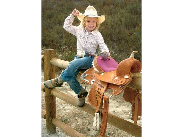 Emma Copenhaver, 6, displays her local and county belt buckles and her state championship saddle at the Hasley Canyon Equestrian Center in Castaic on Friday. Copenhaver is the 2010 California Pee Wee State Champion for the National Barrel Horse Association.