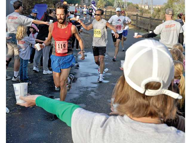 Christina Berretta, in hat and green sleeves, volunteers at a water station at mile 3 of the Santa Clarita Marathon on Sunday. The event, which included races for the marathon, half-marathon and 5 kilometers, was the city's largest, according to officials.