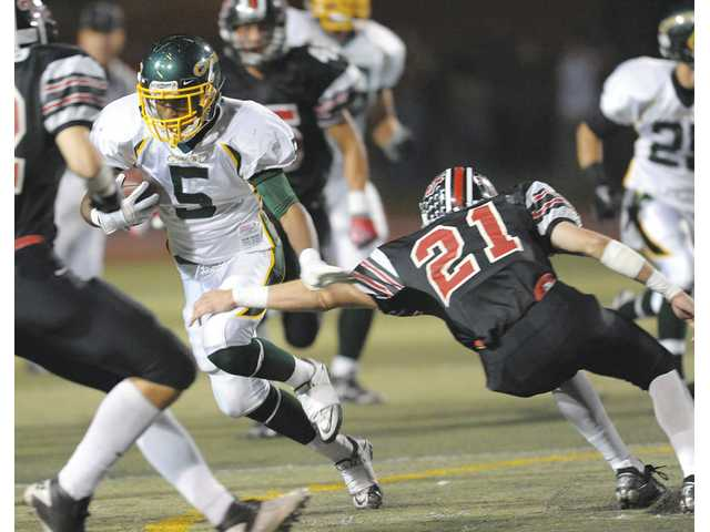 Canyon running back Darius Rudolph (5) breaks the tackle of Hart's Bobby Phillips last Friday at COC.