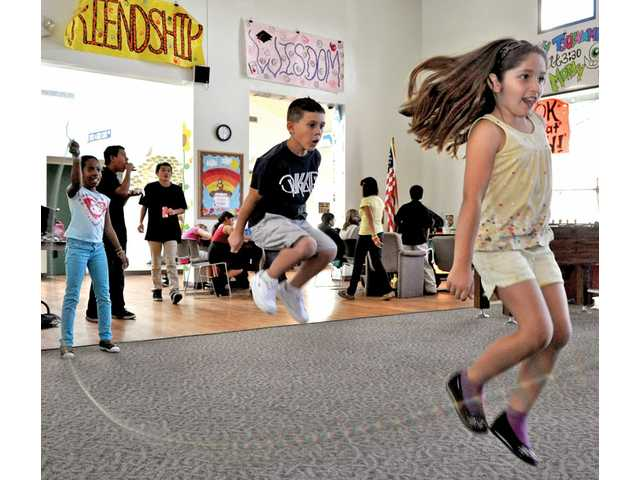 Rachel Espinoza, 8, right, and Zack Guarino, 8, middle, enjoy themselves while jump-roping at the Boys & Girls Club in Newhall, which offers afterschool care for $36 a year.