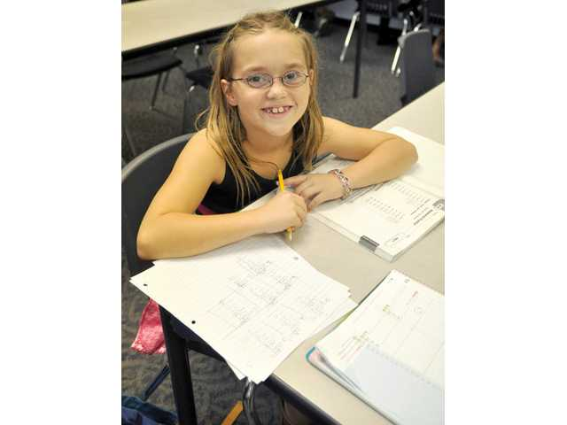 Kaitlyn Witt, 8, takes a break from her math homework. Boys & Girls Club members must finish their homework before taking part in the many activities offered by the club.