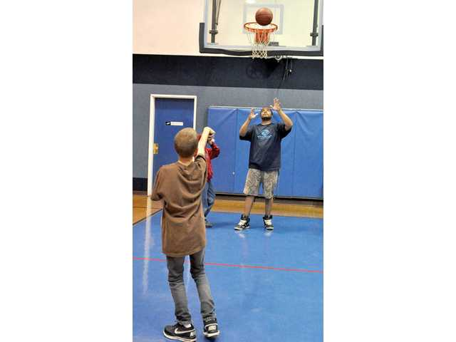 Jacob Hertan, 13, practices free throws with the help of Tyrae Jones, 26.