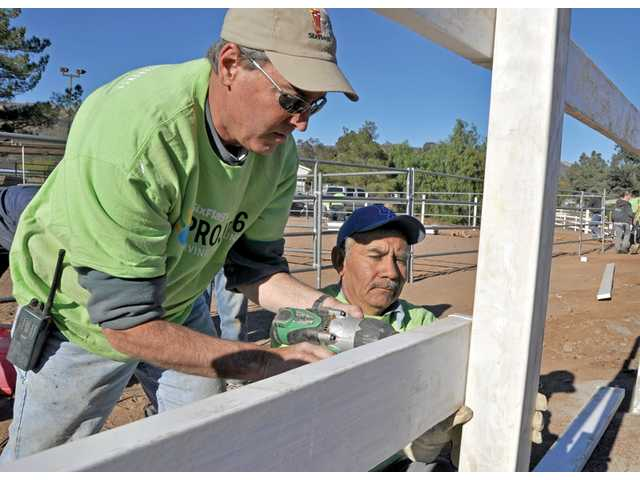 Roland Miller, operations manager for Six Flags Hurricane Harbor, and Francisco Andrade install new fencing at Carousel Ranch in Santa Clarita on Friday.