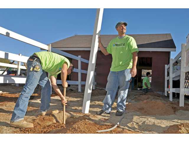 From left, Six Flags employees Mario Barrientos  and Marcus Jackson work on a two-horse corral Friday at Carousel Ranch in Santa Clarita as part of Project 6.