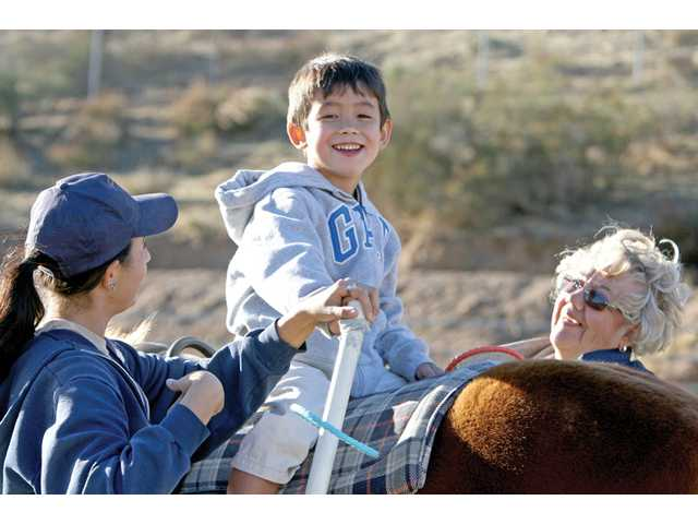 Dee Bender, market research supervisor, helps Caleb Mori, 6,  and ranch instructor Taylor Weinstein enjoy a horseback ride Friday.