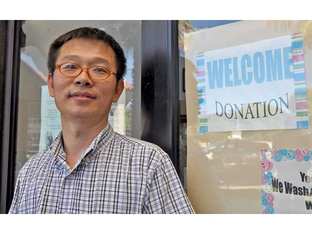 Mike Chang in front of Wayman Cleaners, where he accepts donations of clean clothing and offers the clothing to residents.