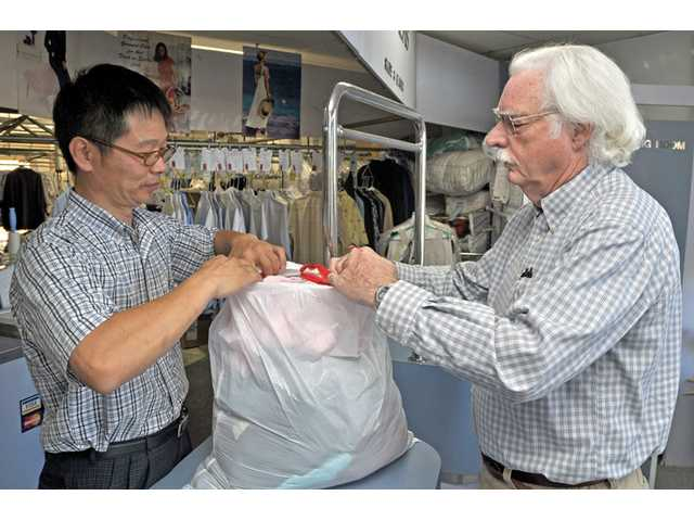 Mike Chang, left, of Wayman Cleaners accepts a bag of clothes from customer David Veal at Chang's store on Lyons Avenue in Newhall.