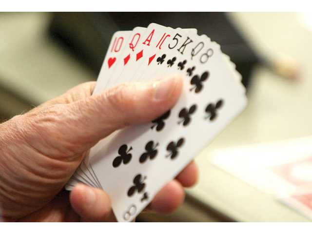 John Swanson holds a hand during a game of bridge.