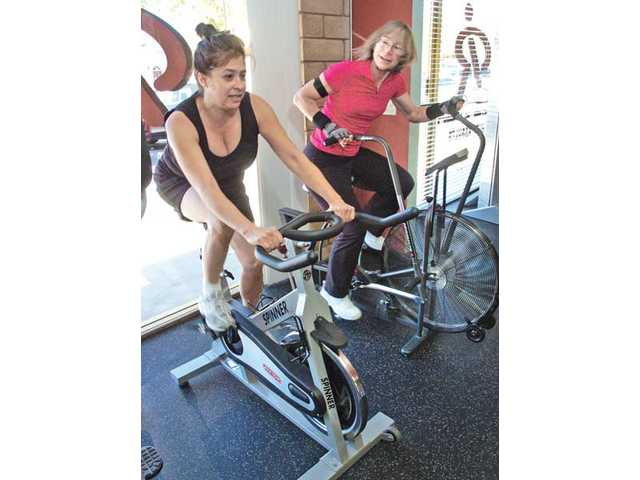 Debbie Banerman, left, and Patty Snowfox exercise on bicycles